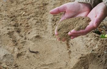 Sand rinnt aus zwei nebeneinander gehaltenen Händen.