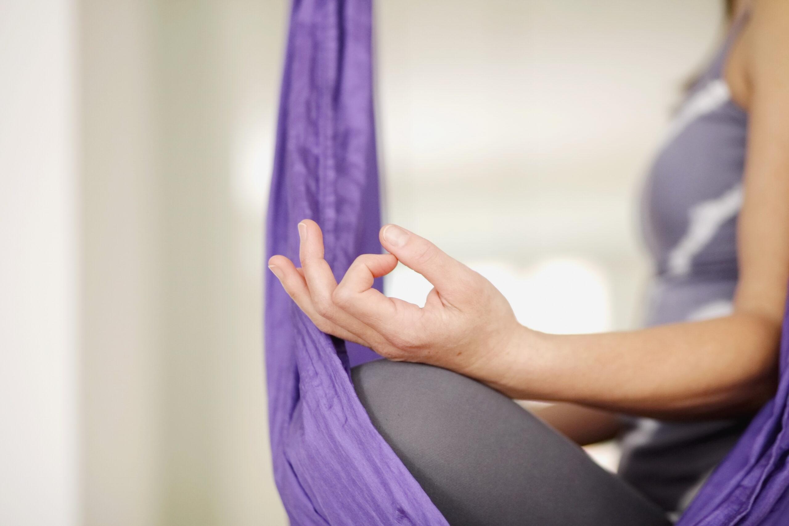 Seitenansicht einer meditierenden Frau im Lotussitz.