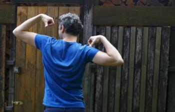Ein Mann mit T-Shirt steht mit angespannten Armen vor einer Holzwand.