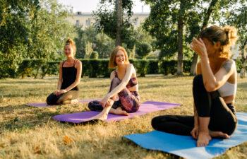 Drei Frauen sitzen lachend auf ihren Yogamatten in der Sonne auf einer Wiese.